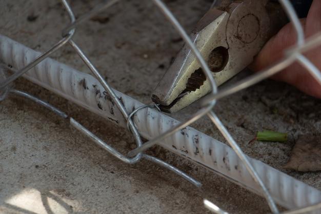 Fixation du bas de la clôture en treillis rectangulaire galvanisé