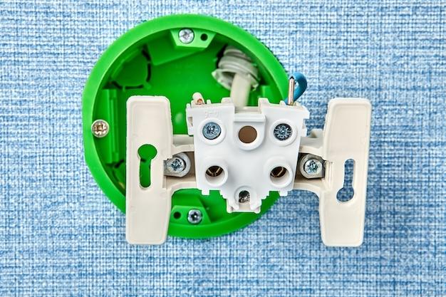 Fixation d'une prise électrique desserrée dans une boîte en plastique.