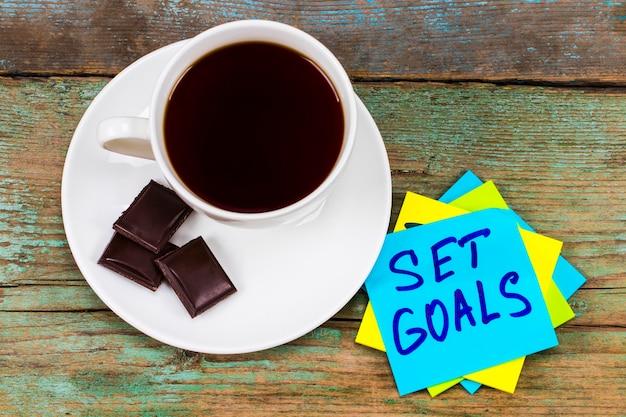 Fixez-vous des objectifs - écriture inspirante dans un post-it vert avec une tasse de café et de chocolat.