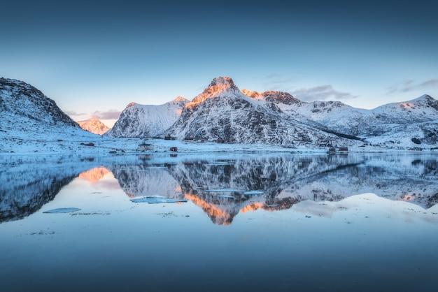 Fjord avec reflet dans l'eau, montagnes enneigées au coucher du soleil