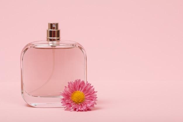 Flacon aux parfums féminins et bouton de fleur sur fond rose. produits pour femmes.