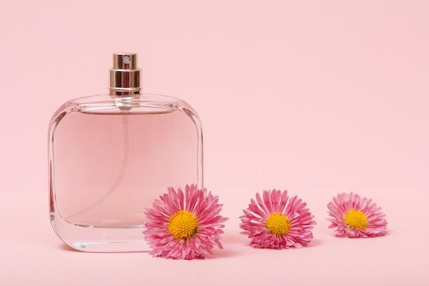 Flacon aux parfums féminins et boutons de fleurs sur fond rose. produits pour femmes.