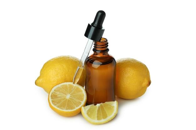 Flacon compte-gouttes avec de l'huile et des citrons isolé sur fond blanc isolé