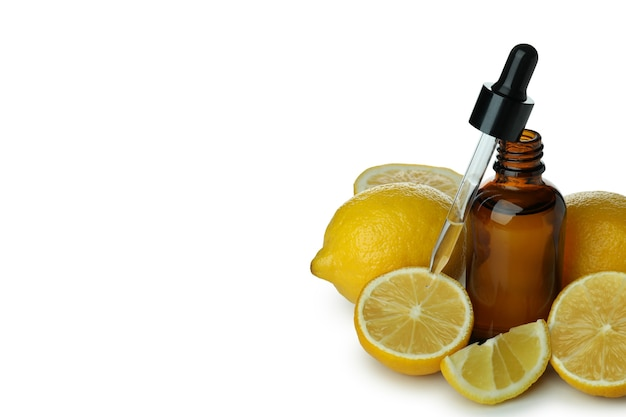 Flacon compte-gouttes avec de l'huile et des citrons isolé sur tableau blanc