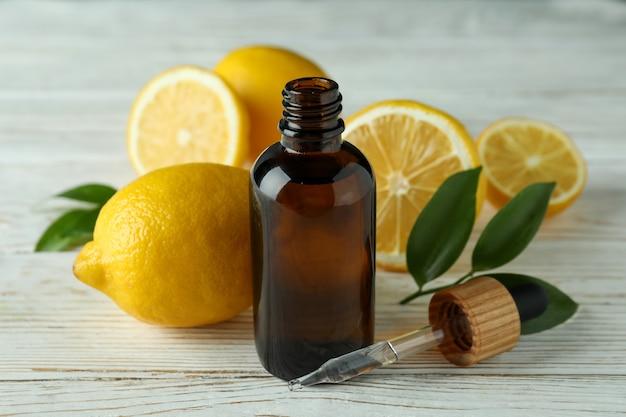 Flacon compte-gouttes avec de l'huile et des citrons sur une table en bois blanc