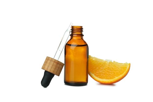 Flacon compte-gouttes avec de l'huile et orange isolé sur tableau blanc