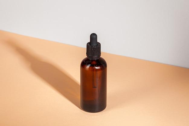 Flacon compte-gouttes de médecine ou d'aromathérapie sur table beige