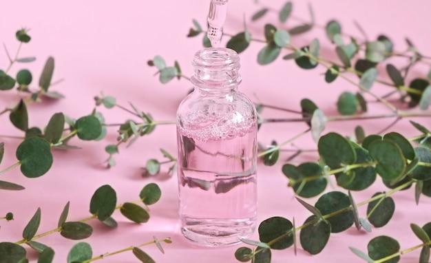 Flacon compte-gouttes en verre avec de l'huile cosmétique naturelle. flacon avec une pipette cosmétique. produit de beauté aux herbes et plantes naturelles. soin de la peau. parfum