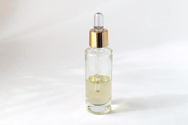 Flacon compte-gouttes en verre avec huile ou sérum cosmétique, fond blanc