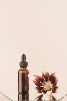 Un flacon compte-gouttes en verre marron et belle fleur sur miroir, fond beige. concept cosmétique de spa bio naturel. vue de face.
