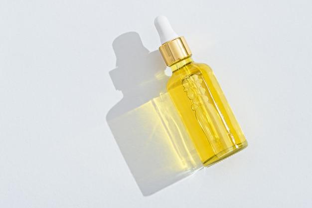 Flacon cosmétique compte-gouttes avec pipette sur fond blanc avec espace de copie