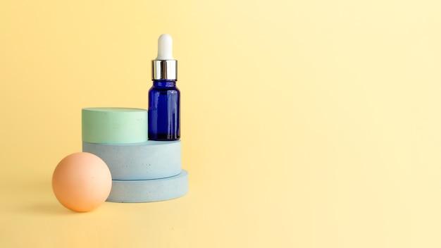 Flacon cosmétique en verre bleu avec compte-gouttes, restant sur le podium. couleurs pastel, socles de forme géométrique. place vide pour les produits d'affichage. maquette cosmétique, grande bannière.
