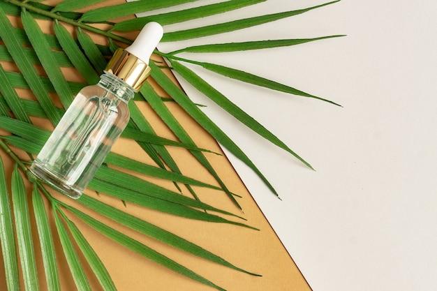 Un flacon cosmétique en verre avec un compte-gouttes sur fond beige avec des pierres et des feuilles.