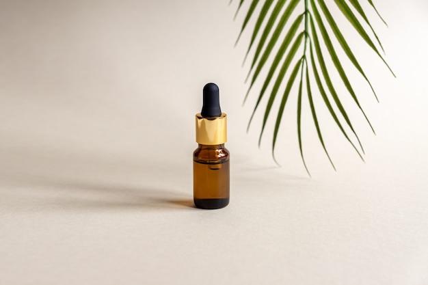 Un flacon cosmétique en verre avec un compte-gouttes sur une surface grise avec feuille de palmier