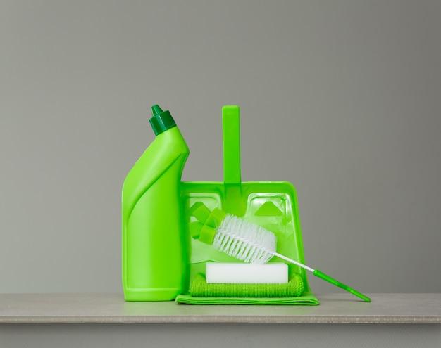 Flacon de détergent vert pour toilette, brosse, éponge, cuillère et poussière sur gris