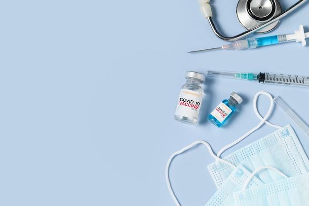 Un flacon du vaccin covid 19 avec seringue et stéthoscope sur un masque chirurgical sur fond bleu, prévention du coronavirus ou concept d'épidémie de covid-19