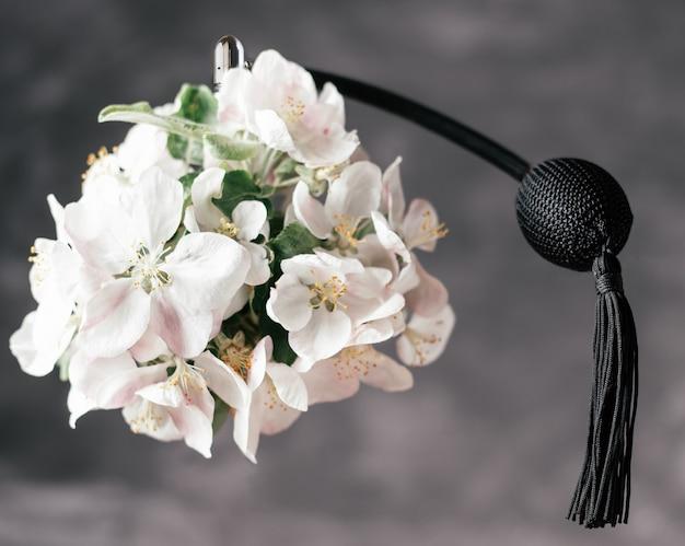 Flacon d'eau de toilette ou de parfum à base de fleur de pommier avec une longue pompe à pompon noir s'élève dans l'air sur fond gris foncé
