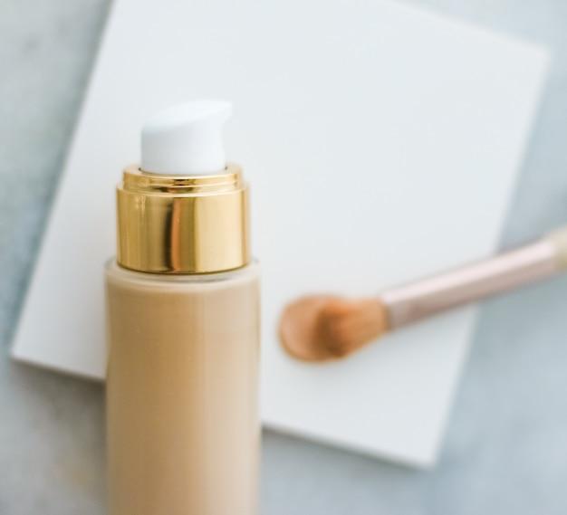 Flacon de fond de teint maquillage glamour et concept de soins de la peau de marque cosmétique et pinceau de contour sur mar ...