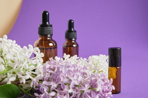 Flacon marron avec applicateur en métal à bille pour parfum artisanal et lilas sur fond violet vif, huiles et parfum avec concept parfum lilas