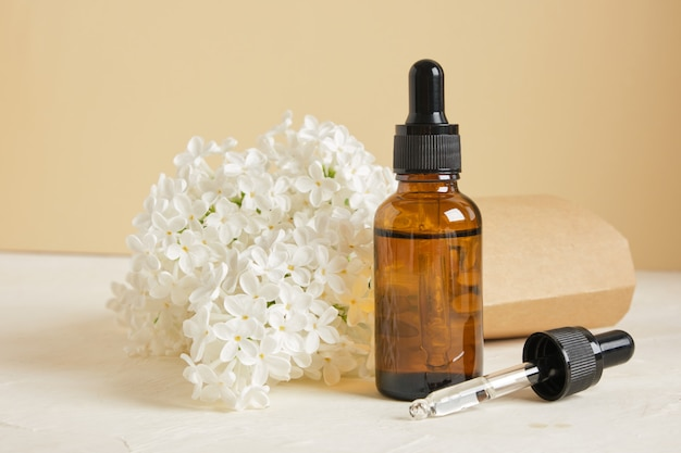 Flacon marron avec compte-gouttes pour huiles ou sérums cosmétiques et branche de lilas blanc sur fond beige, cosmétiques naturels pour les soins de la peau du corps et du visage.