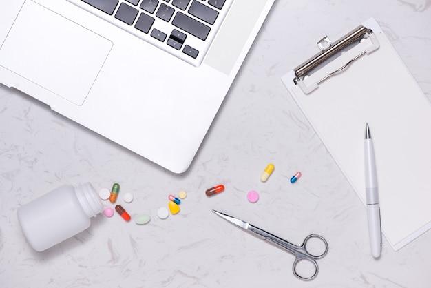 Flacon de médicament ouvert et capsules renversées sur une table avec du papier vierge et un ordinateur portable.