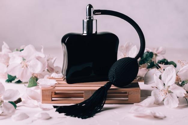 Flacon noir eau de toilette ou parfum avec pompe à pompon sur palette en bois sur plâtre clair avec fleurs de pomme