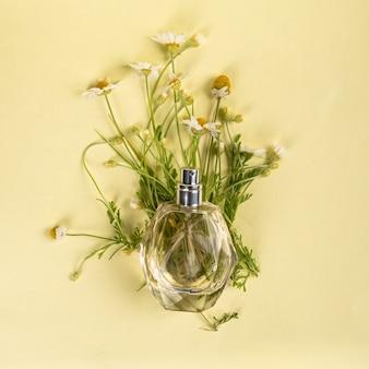 Flacon de parfum au parfum de camomille sur fond jaune à plat.