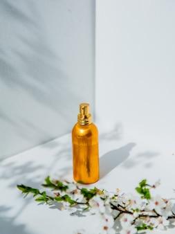 Flacon de parfum et branche de cerisier avec des fleurs dans un coin blanc