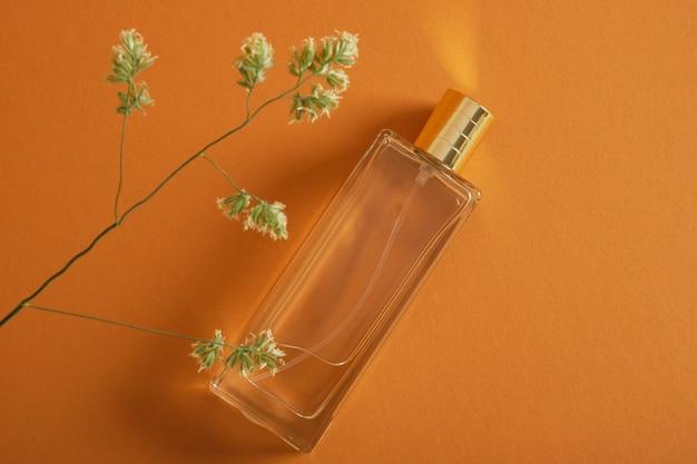 Flacon de parfum et brin d'herbe sur fond marron