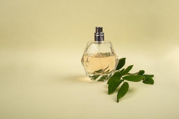 Flacon de parfum avec un brin de rose sur fond jaune, soins de la peau de beauté.