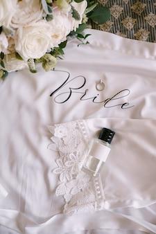 Un flacon de parfum avec un capuchon noir une alliance avec une pierre et un bouquet de roses blanches