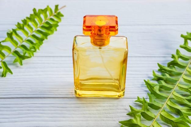 Flacon de parfum doré sur un tableau blanc