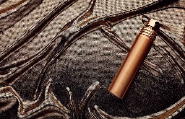 Flacon de parfum doré sur un tissu doré