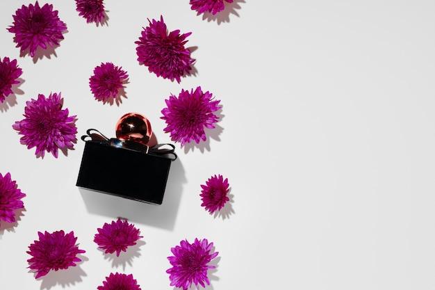 Flacon de parfum entouré de boutons floraux close up