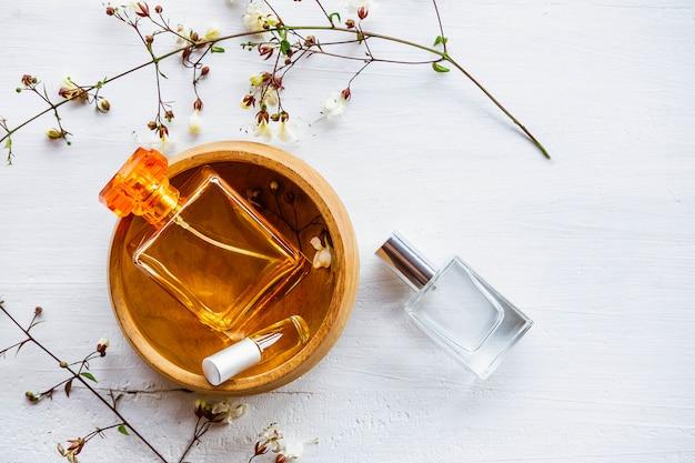 Flacon de parfum avec des fleurs sur un fond en bois blanc