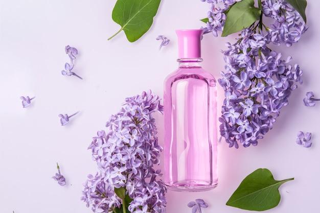 Flacon de parfum avec des fleurs lilas sur mur blanc