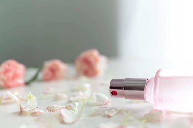 Flacon de parfum avec des fleurs d'oeillets sur une table blanche.