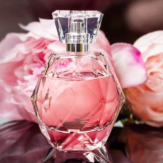 Flacon de parfum avec des fleurs sur une surface sombre