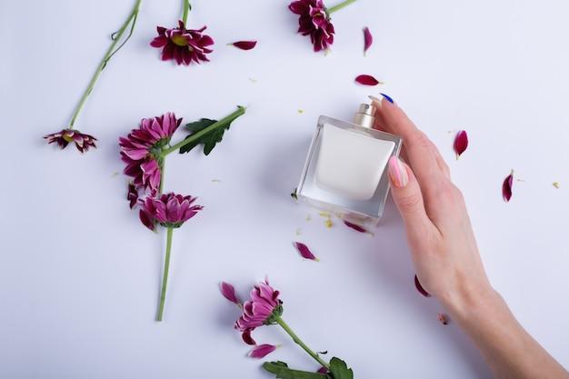 Flacon de parfum avec des fleurs sur un tableau blanc