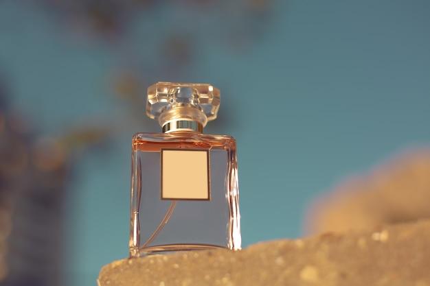 Flacon de parfum sur fond de ciel bleu