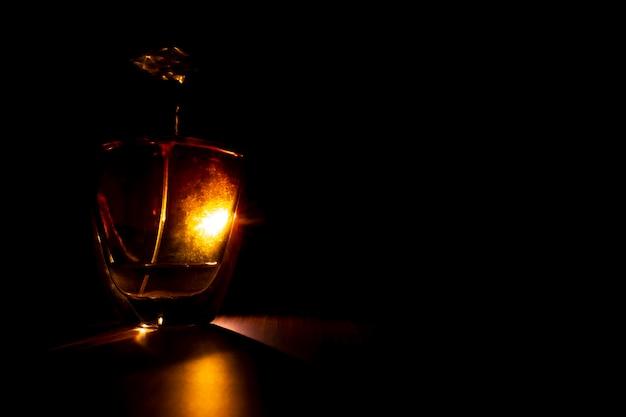 Flacon de parfum haut de gamme isolé sur fond sombre avec rétro-éclairage