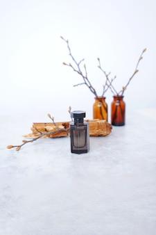 Flacon de parfum noir sur fond d'écorce et de branches en bois