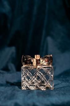 Flacon de parfum parfumé femme sur un tissu bleu foncé