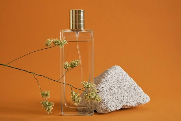 Flacon de parfum, pierre et brin d'herbe sur fond marron