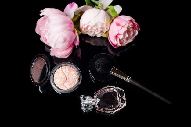 Flacon de parfum, pinceau de maquillage et fard à joues avec des fleurs