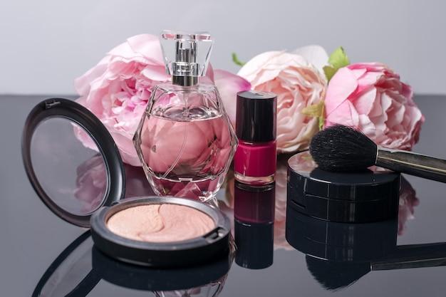 Flacon de parfum, pinceau de maquillage, vernis à ongles et fard à joues avec des fleurs