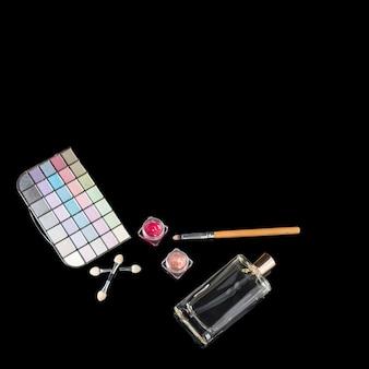 Flacon de parfum, pinceaux de maquillage, palette d'ombres à paupières de maquillage et rouges à lèvres