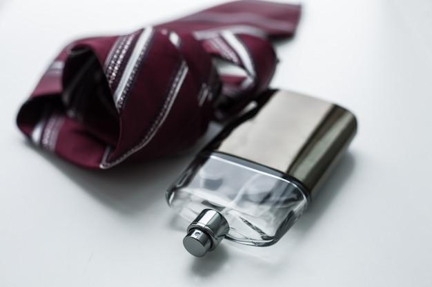 Flacon de parfum pour homme avec cravate sur fond blanc.