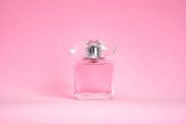 Flacon de parfum pulvérisé sur fond pastel rose