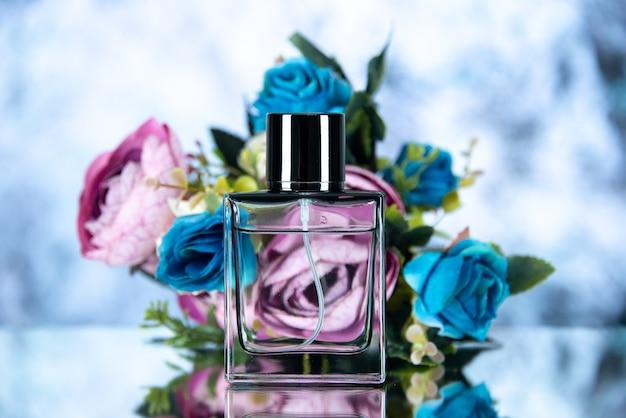 Flacon de parfum rectangle vue de face fleurs colorées sur fond flou bleu clair
